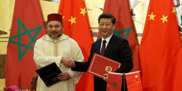 China's President Xi Jinping (R) and Moroccan King, Mohammed VI, shake hands after signing documents...