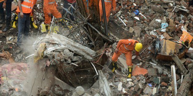 Indian rescue workers and fire officials look for survivors in debris at the site of a building collapse...