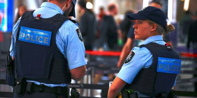 Australian Federal Police officers stand near the check-in counters at the Sydney Airport Domestic terminal...