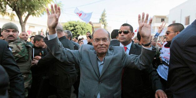 Tunisia's President Moncef Marzouki, who is seeking re-election, greets supporters during a presidential...