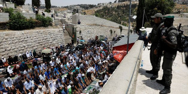Israeli border police officers stand guard as Palestinians pray at Lions' Gate, the entrance to Jerusalem's...