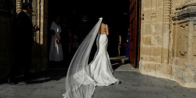 A woman walks into a church before getting married in the white village of Espera, southern Spain September...