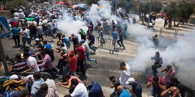 JERUSALEM, ISRAEL - JULY 21: (ISRAEL OUT) Palestinian worshippers run for cover from teargas, fired by...