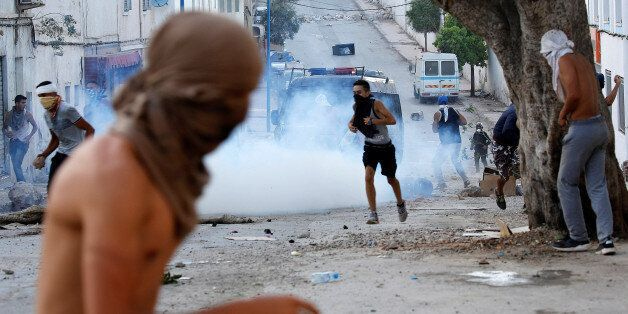 Protesters throw stones against riot police during a demonstration against alleged corruption in the...