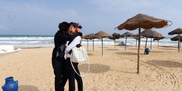 A young Tunisian couple kiss on the empty beach of Hammamet as thousands of Tunisian tour operators and...