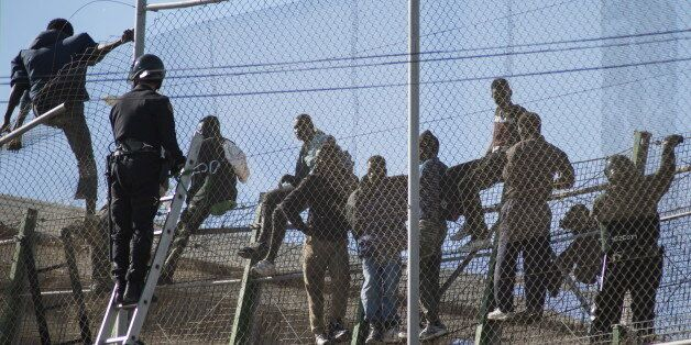 African migrants sit on top of a border fence during an attempt to cross into Spanish territories, between...
