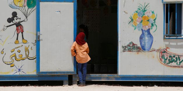 A Syrian girl looks into a room at a school run by Relief International in Al Zaatari refugee camp outside...
