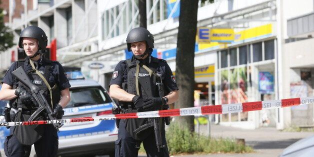 Police cordon off the area around a supermarket in the northern German city of Hamburg, where a man killed...
