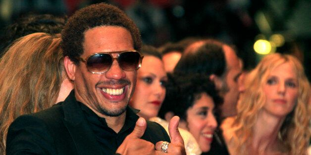 Actor Joey Starr gestures as he arrives on the red carpet for the screening of the