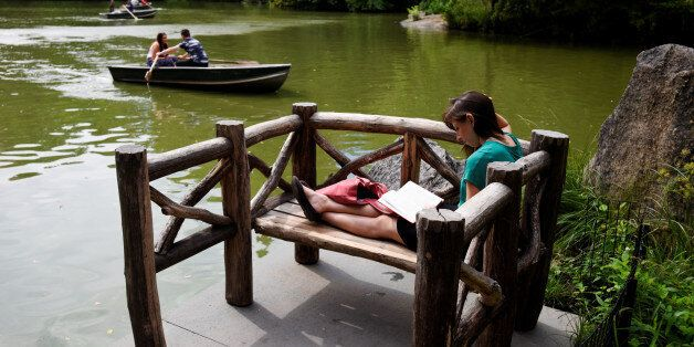 Evin Lawson reads a book as people paddle row boats on the lake in Central Park during mild weather at...