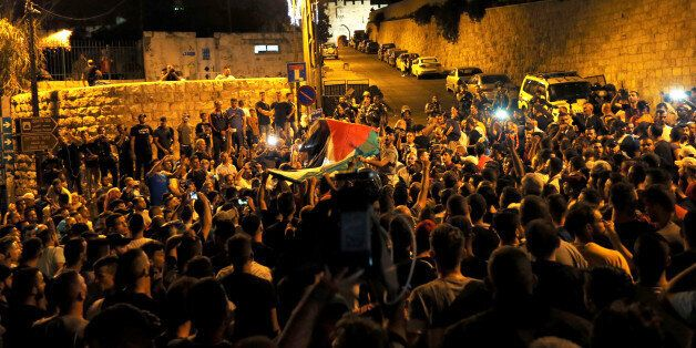 Palestinians celebrate outside Lion's gate at the entrance to Jerusalem's Old City following Israel's...