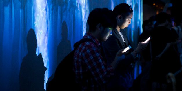 TOKYO, JAPAN - JULY 27: Visitors use smartphones as they stand in front of a digital installation produced...