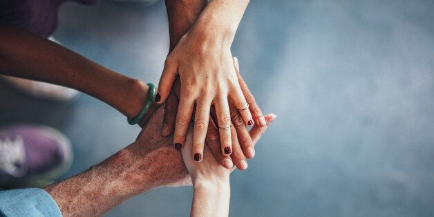 Multiethnic group of young people putting their hands on top of each other. Close up image of young students...