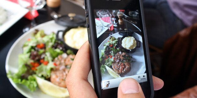 A man takes a picture with his mobile of foods in his plate as he is having lunch on July 19, 2012 in...