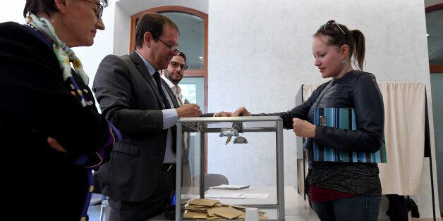 A French national residing in Tunisia casts her vote for the first round of the French presidential election...