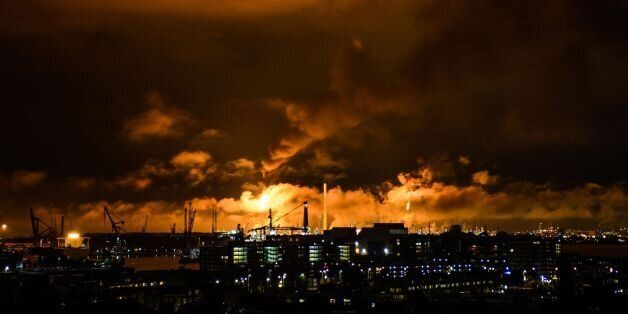 A photo taken at night on July 29, 2017 shows flames and smoke rising above the Shell refinery in Rotterdam.A...