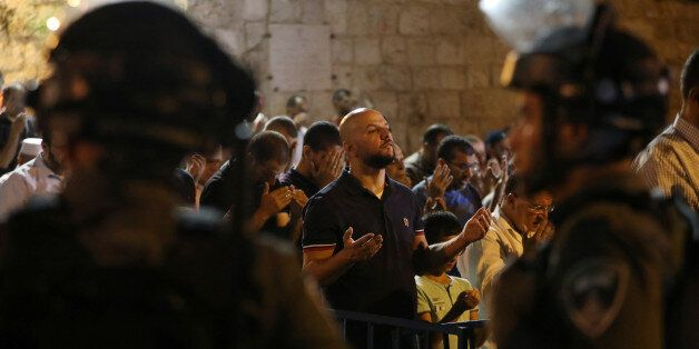 Israeli border police stand guard as Palestinians take part in evening prayers outside the Lion's Gate...