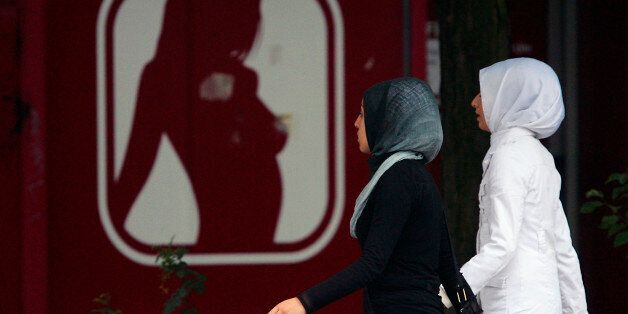 Girls with headscarves walk past a sex shop in Berlin July 12, 2007. Chancellor Angela Merkel's cabinet...