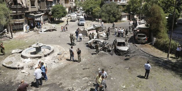 Syrians gather to inspect the damage at the site of a suicide bomb attack in the capital Damascus' eastern...