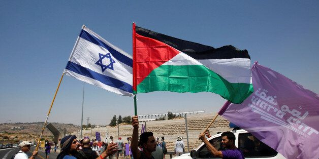 Palestinian and Israeli activists take part in a protest demanding end of Israeli occupation and calling...