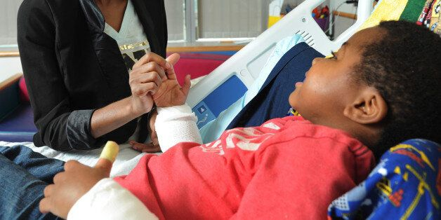 Pattie Ray holds the new right hand of her son, Zion Harvey, 8, in his hospital bed on July 27, 2015,...