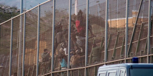 African migrants scale back over a border fence between Morocco and Spain's north African enclave Melilla...