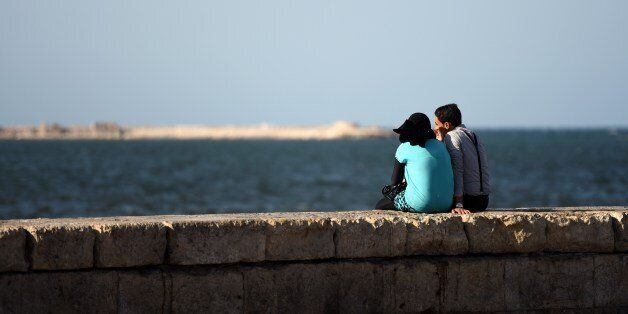 An Egyptian couple sits on a wall by the sea on September 12, 2015 in the Egyptian port city of Alexandria....