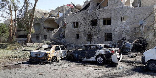 Damaged cars are seen at one of the blast sites in Damascus in this handout picture posted on SANA on...