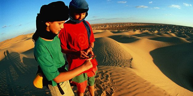 (GERMANY OUT) Tunisia - Boys on a trekking tour navigating in the Grand Erg Oriental. (Photo by Knut...