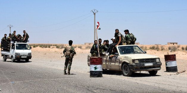 A picture taken on July 8, 2017 shows members of the Syrian pro-government forces riding in vehicles...