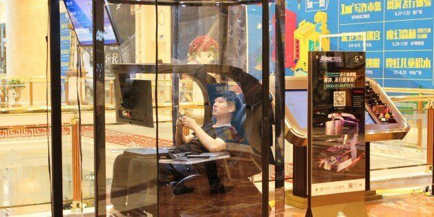 This photo taken on July 14, 2017 shows a man playing video games in a booth at a shopping mall in Shanghai.China...