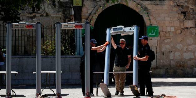 Israeli border policemen install metal detectors outside the Lion's Gate, a main entrance to Al-Aqsa...