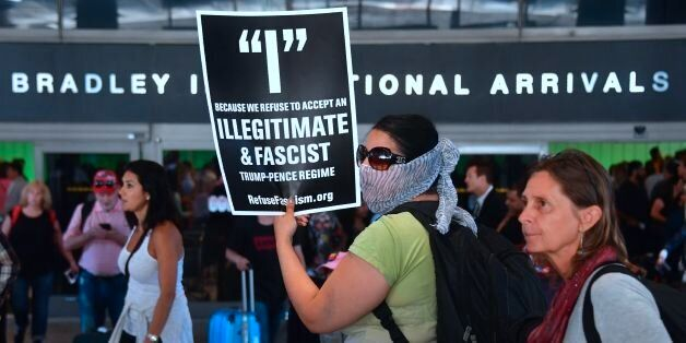 Activists hold placards outside the International Arrivals section at Los Angeles International Airport...
