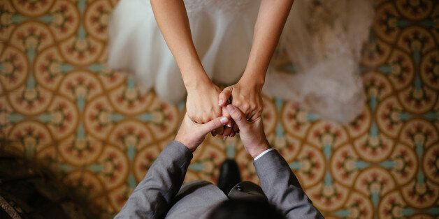 A close up shot of a bride and groom holding hands from a top