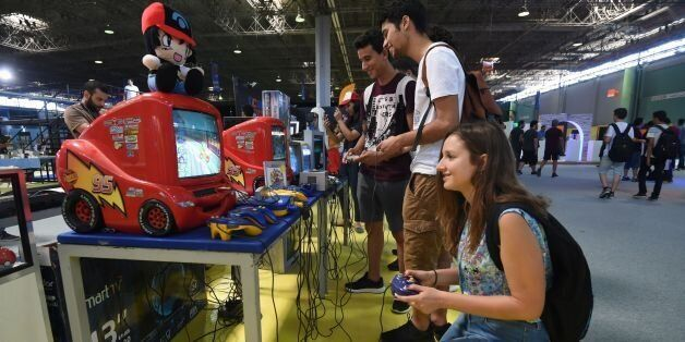 Young Tunisians play on a Nintendo 64 console during the opening of the second edition of Comic Con Tunisia...
