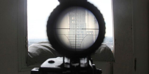 A view seen through the scope of a weapon belonging to a sniper and rebel fighter shows a building where...