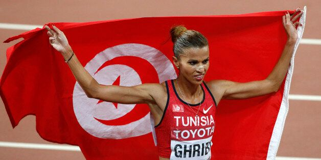 Habiba Ghribi of Tunisia holds her national flag after finishing second in the women's 3000 metres steeplechase...