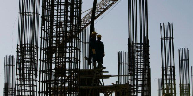 Workers stand on steel reinforcements at a hospital building site during Algeria's President Abdelaziz...
