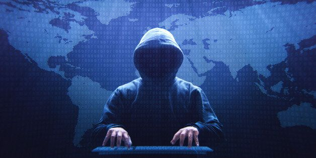 Anonymous computer hacker sitting in front of a virtual