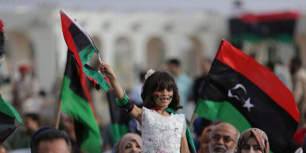A girl holds a Libyan flag during celebrations marking the third anniversary of Libyan National Army's...