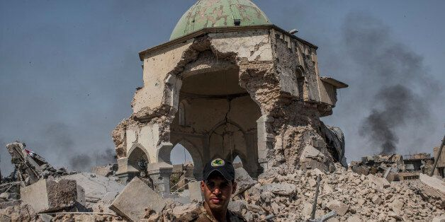 MOSUL, IRAQ - JUNE 30: An Iraqi ISOF forces soldier in front of the destroyed al-Nuri mosque in the Old...