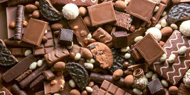 Chocolate background. Many pieces of chocolate, candies, cookies, biscuits, cakes and other sweets. Milk...