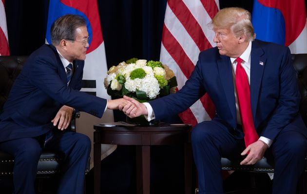 US President Donald Trump (R) shakes hands with Korean President Moon Jae-in during a meeting on the...