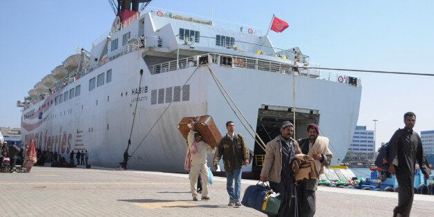Egyptian workers who fled the unrest in Libya and were stranded in Tunisia, carry their baggage upon...