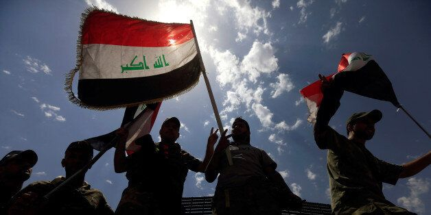 Members of the Emergency Response Division wave Iraqi flags as they celebrate in the Old City of Mosul,...