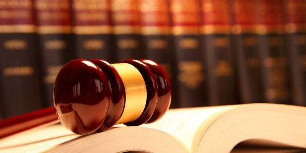 A wooden gavel rests on top of an open law book in front of a row of law books that is out of focus in...