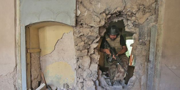 A member of the Iraqi Counter-Terrorism Service (CTS) walks through the rubble and the broken wall of...