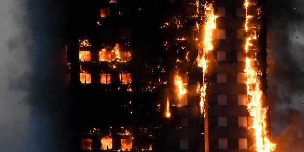 Flames and smoke billow as firefighters deal with a serious fire in a tower block at Latimer Road in...