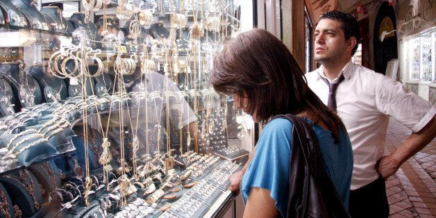 A Tunisian couple looks at the display in a jewelry shop window in the souk of Medina on September 14,...