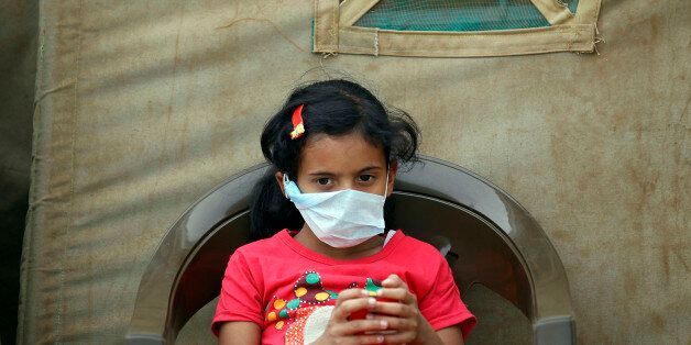 A Yemeni child suspected of being infected with cholera sits outside a makeshift hospital in Sanaa on...